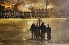 Orthodox priests standing between Ukrainian protesters and Ukrainian police